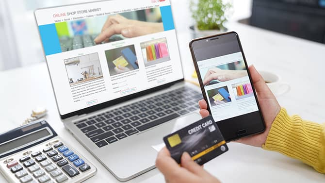 Almost all online activities can contribute to your digital footprint. Image shows somebody holding their phone and credit card up in front of a computer screen with an online shopping window open.